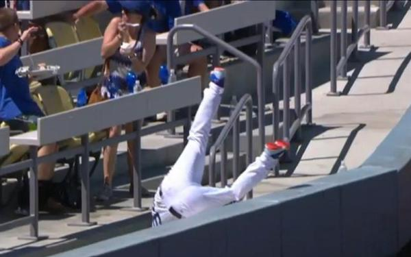 Dodgers worker Javier Herrera takes a fall, and fans raise him up